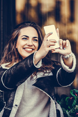 Happy young woman making selfie photo on smartphone