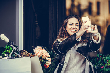Young woman making selfie photo on smartphone