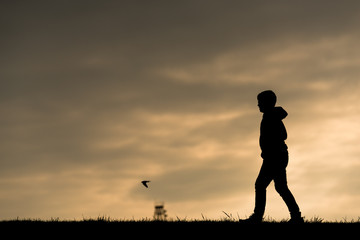 silhouette of a child on a dike