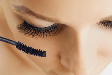 Female eye with extreme long eyelashes and brush of mascara. Make-up, cosmetics, beauty