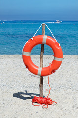 Orange life buoy on the sandy beach against blue sea water