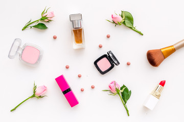 Makeup products for young girls. Composition with cosmetics with rose tones. Lipstick, bulk, eyeshadow, perfume, brushes and rose flowers on white background top view