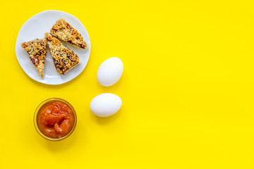 Ingredients for homemade cookies. Fresh cookies near jam, eggs on yellow background top view copy space