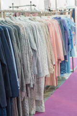 warm winter demi raglans on white shopping racks with silver metal parts on clothes shop. bright different clothes on the rack before sale season. new collection in clothes luxury shop
