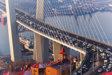 Golden cable-stayed bridge road car traffic from above. Modern Vladivostok Russia night illumination. Old and modern central buildings.