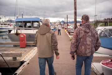 Two senior walk together at a marina