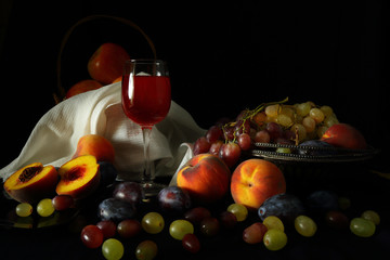 Still life with fruit and a glass of wine on a dark background
