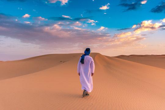 Berber man wearing traditional tuareg clothes in the Sahara Desert at dawn, Merzouga, Morocco