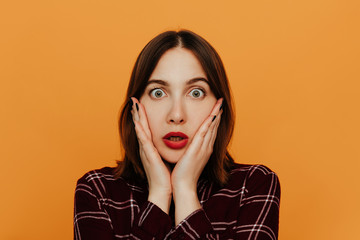 Woman portrait. Emotions. Girl is looking at camera, hands on cheeks, shock in her eyes, on an orange background