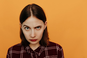 Woman portrait. Emotions. Girl is raising her eyebrow and looking at camera, on an orange background