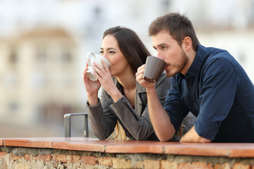 Couple drinking coffee watching views in a balcony