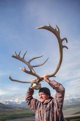A senior man holding a rack of elk antlers