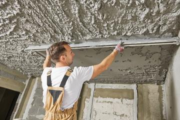 Plasterer smoothing plaster mortar on ceiling with screeder