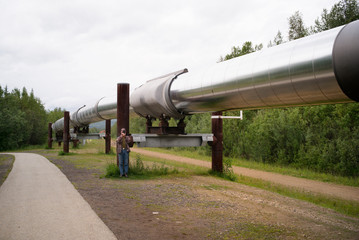 A man takes a photo of an oil pipeline