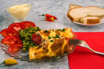 Omelette of eggs in a roll with meat filling. Green peas. A dish of Italian cuisine - brizoli. Light background.