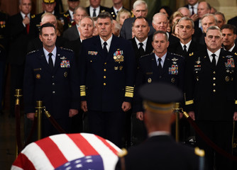Members of the military stand at attention as they look at the flag-draped casket of former President George H.W. Bush inside the Rotunda in the US Capitol during the State Funeral in Washington