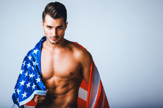 Portrait of shirtless handsome young man with stylish haircut posing with American flag over gray background. Perfect hair & skin. Close up. Studio shot