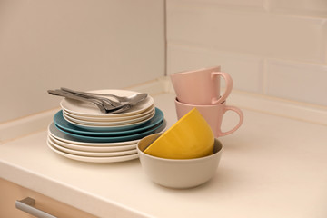 Clean dishware and cutlery on counter in kitchen