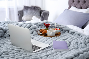 Laptop, notebook and tray with breakfast on bed in stylish room interior
