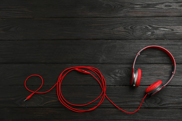 Stylish modern headphones and space for text on wooden background, top view