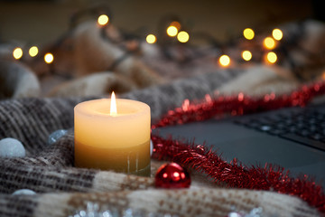 Candle and Christmas garland on a blanket. Selective focus