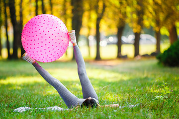 Beautiful sport fitness girl in sportswear doing fitness exercise with pink ball for fitness in the park.