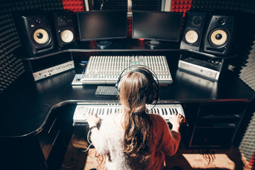 young woman is working in the music studio. close up back view shot. girl in headphone learning to play in the synthesizer.instrument