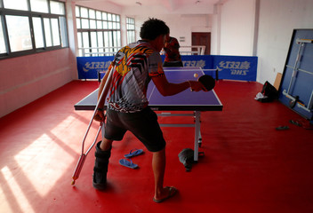 Injured Papua New Guinea table tennis player David Loi hits a ball as he practices with team mate Goada Elly at a Beijing-funded facility in central Port Moresby