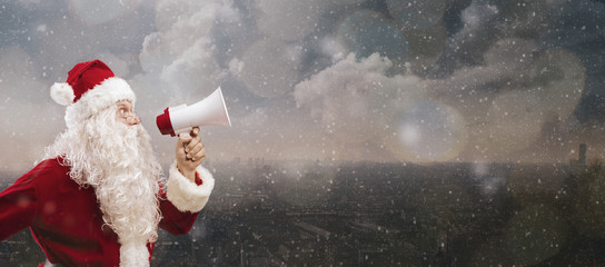 Santa shouting with a megaphone under the snow
