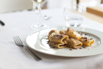 Close up on a dish with italian paccheri pasta, served on a restaurant table