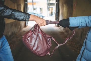 Robber snatches bag from hands of woman, close up. Criminal pickpocket and crimes on city street