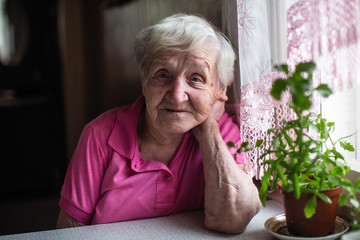 Elderly woman sitting at the table in home.