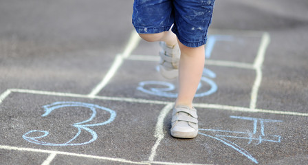 Closeup of little boy's legs and hopscotch drawn on asphalt