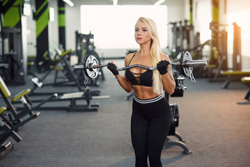 Attractive sexual female in sports wear doing biceps exercises with barbell at the modern gym. Sporty and healthy concept.
