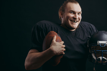 Dramatic portrait of american football player smiling, showing broken front tooth holding his helmet and ball in arms background