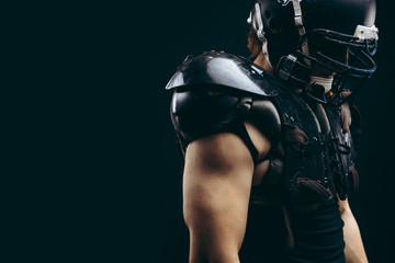 Shirtless American football player with wearing helmet and protective shields on naked body, half size portrait over black wall, profile view