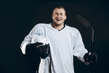 Happy Handsome hockey player with one broken front tooth laughing at camera, standing with stick in white uniform, isolated on black