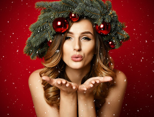 Beautiful woman with Christmas spruce fir wreath with cones and new year decoration red balls