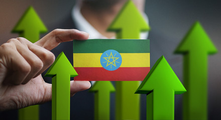 Nation Growth Concept, Green Up Arrows - Businessman Holding Card of Ethiopia Flag