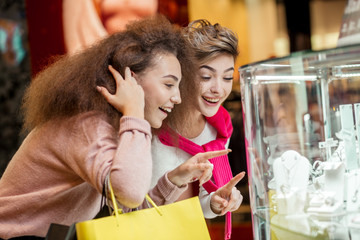 Two happy excited young ladies having fun doing shoppings in golden jewelry shop, they point at showcase and choose jewelry, imagine how it looks on them, close up