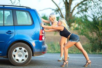two beautiful blonde girls  on high heels are pushing broken car