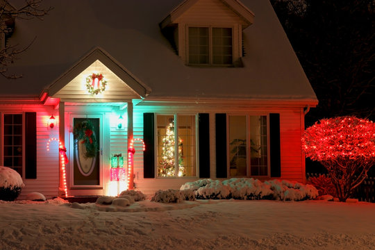 Seasonal house outdoors decoration. Background with house main entrance and front yard, covered by fresh snow decorated for Christmas and New Year Holidays. Decorated christmas tree in the window.