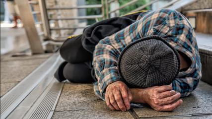 poor homeless beggar sleeping on pathway floor in suffering of unemployment asking for help Fototapete