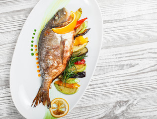 Grilled dorado fish with baked vegetables and rosemary on plate on wooden background close up. Healthy food. Top view