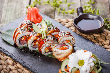 Sushi rolls set with smoked eel, red caviar, sesame and wasabi on black stone on bamboo mat, selective focus. Japanese cuisine