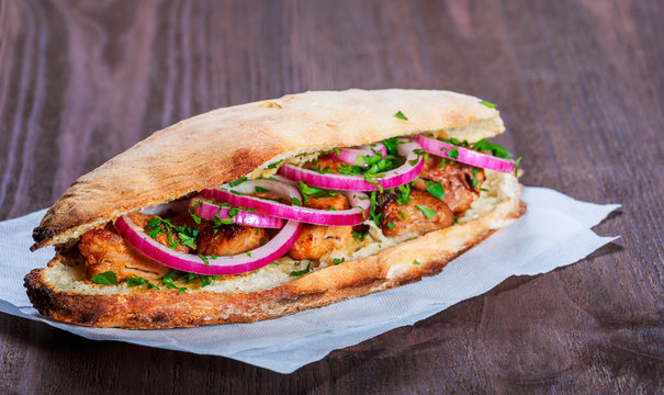 Grilled chicken in sandwich from fresh pita bread with onion and greens on dark wooden background. Shashlik or Shish kebab. Healthy lunch