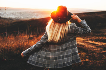 Back view of young female in stylish hat and jacket standing in beautiful countryside during wonderful sundown.Unrecognizable elegant lady in countryside during sunset