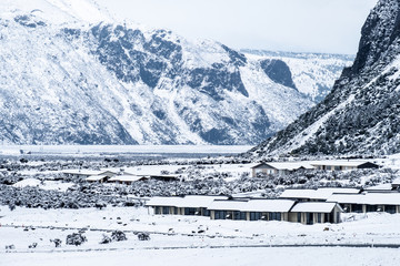 View of the houses in Mount Cook Village covered with white fresh snow in a snowy day.
