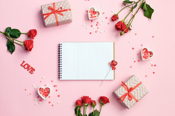 Open blank notebook with gift box, flowers and hearts on a pink background. Valentines day background.