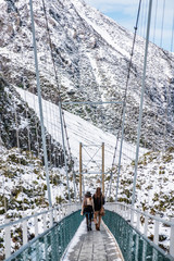 People crossing the river by a swing bridge. Hooker Valley Track covered with white snow after a snowy day. Mount Cook National Park.
